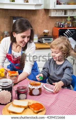 Smiling mother and little boy having a snack and talking in the kitchen.  - stock photo