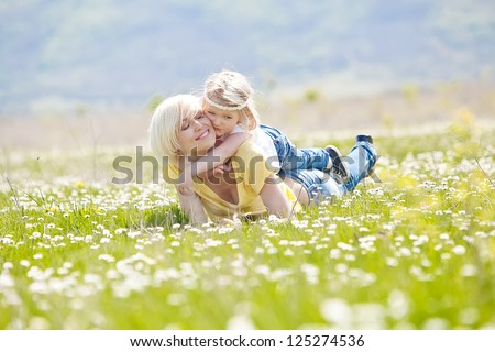 Smiling mother and little daughter on nature. Happy people outdoors