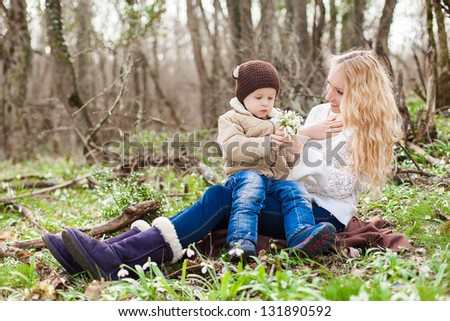 Smiling mother and little son on grass and snowdrops in park