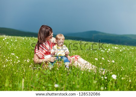 Smiling mother and little son on nature. Happy people outdoors