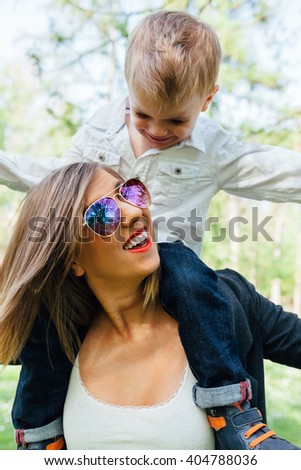 Smiling mother and little son playing together in a park. Happy family, friends forever concept.