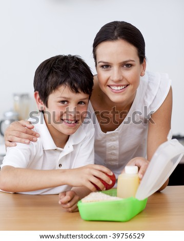 Smiling mother and son making the school lunch in the kitchen - stock photo
