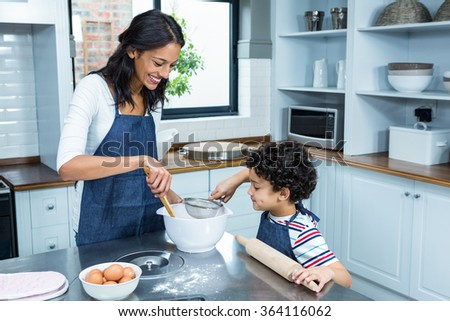 Smiling mother cooking with her son in kitchen at home - stock photo