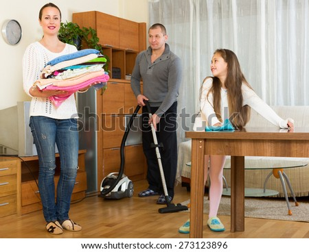 Smiling mother, father and  girl doing general cleaning indoors - stock photo