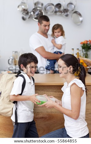 Smiling mother giving school lunch to her son in the kitchen - stock photo