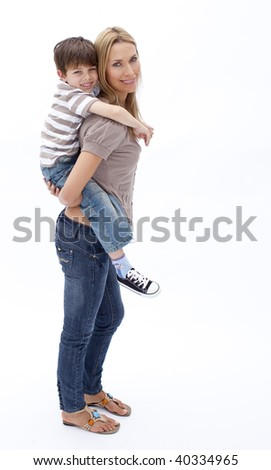Smiling mother giving son piggy back ride against white background