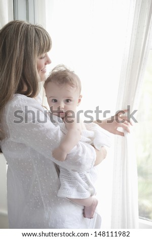 Smiling mother holding baby boy while looking through window - stock photo