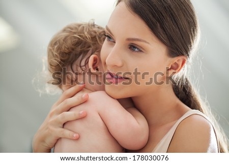 Smiling mother holding her cute baby boy. - stock photo