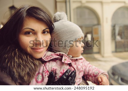 smiling mother holding her cute daughter - stock photo