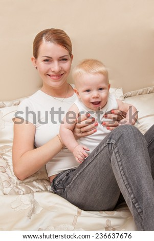 Smiling mother holding her happy baby while they both sitting on the bed. Selective focus on the baby