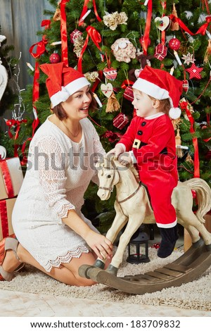 Smiling mother in santa cap sits under Christmas tree near rocking horse  on which little girl in santa suit sits - stock photo