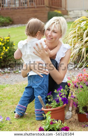 Smiling mother looking at her child standing in the garden