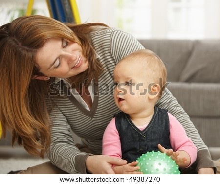 Smiling mother playing with little girl holding ball at home. - stock photo