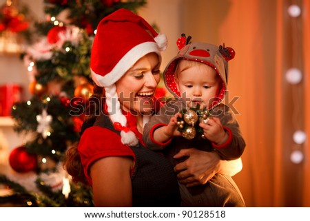 Smiling mother playing with lovely baby near Christmas tree - stock photo