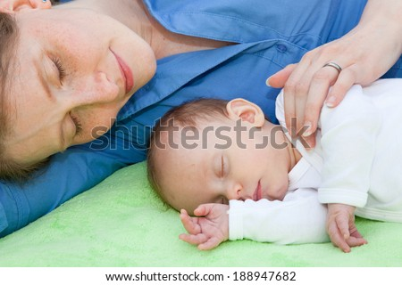 Smiling mother sleeping with her beautiful little newborn baby keeping a protective hand on its shoulder as they rest peacefully together