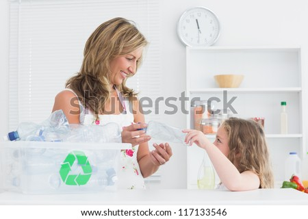 Smiling mother sorting waste with her daughter - stock photo