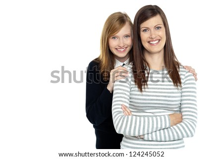 Smiling mother standing with her hands crossed and daughter embracing her from behind. - stock photo