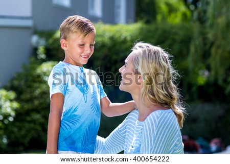 Smiling mother talking to son at backyard