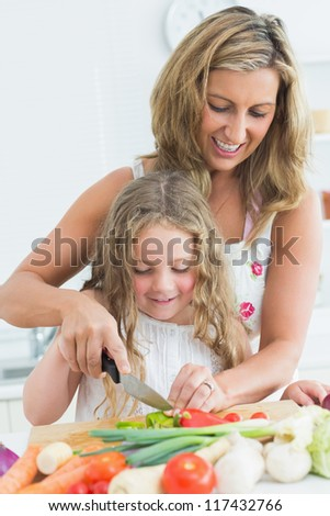 Smiling mother teaching her daughter cutting various vegetables