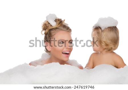 Smiling mother with her daughter and soap foam isolated on white