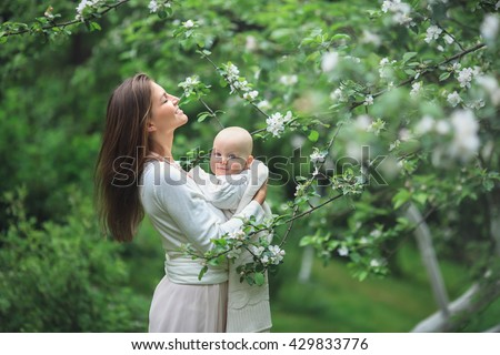 smiling mother with long hair in dress hugging a cute baby in a blanket standing in a flowering garden - stock photo