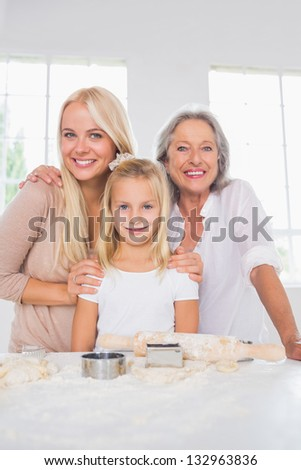 Smiling mothers and daughters cooking together in the kitchen - stock photo