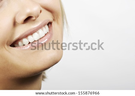 Smiling mouth with perfect white teeth of a young woman wearing natural lip gloss with a lovely skin, isolated on white with copy space