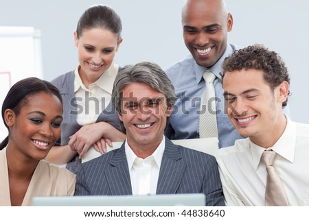 Smiling Multi-ethnic business group using a laptop in the office
