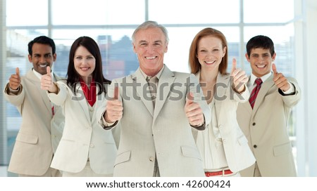 Smiling multi-ethnic business team with thumbs up in a business building - stock photo