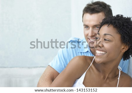 Smiling multiethnic couple leaning together against wall - stock photo