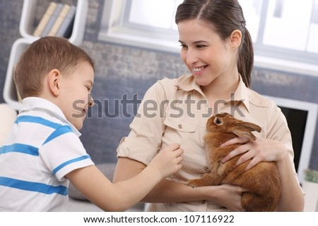 Smiling mum and little son playing with pet rabbit at home.