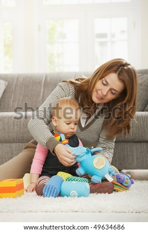 Smiling mum playing with baby daughter on floor of living room.