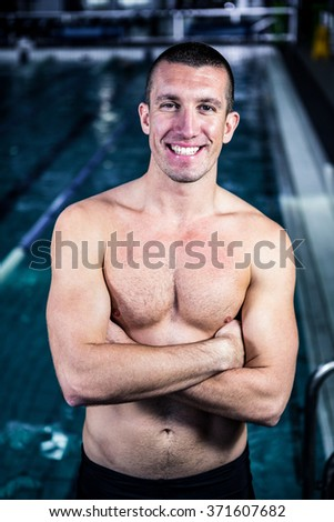 Smiling muscular swimmer with arms crossed in swimming pool - stock photo