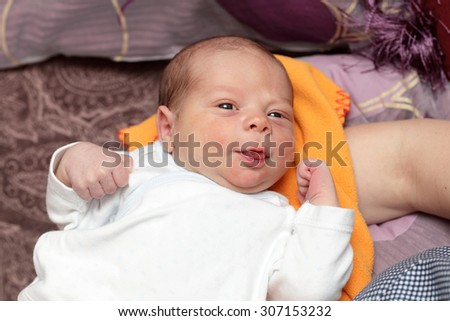 Smiling newborn lying on the blanket at home
