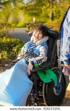 Smiling nine year old boy in wheelchair enjoying time at park outdoors - stock photo