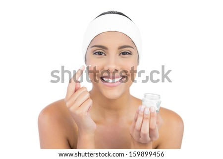 Smiling nude brunette using moisturizer looking at camera on white background