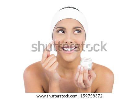 Smiling nude brunette using moisturizer looking away on white background