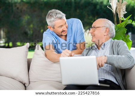 Smiling nurse and senior man looking at each other while using laptop at nursing home porch - stock photo