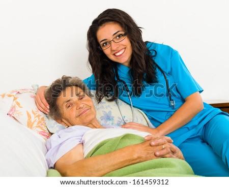 Smiling nurse caring for kind elder patient in nursing home. - stock photo