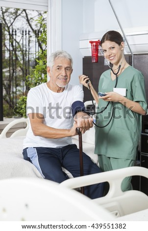 Smiling Nurse Checking Blood Pressure Of Patient In Rehab Center - stock photo