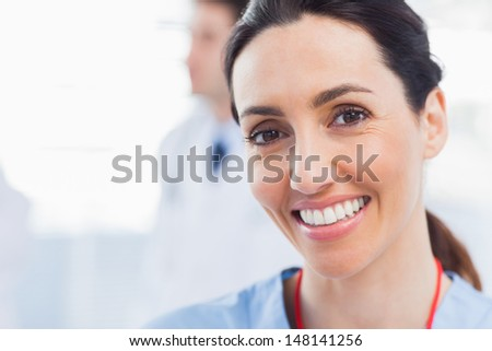 Smiling nurse looking at camera with a doctor behind her in medical office - stock photo