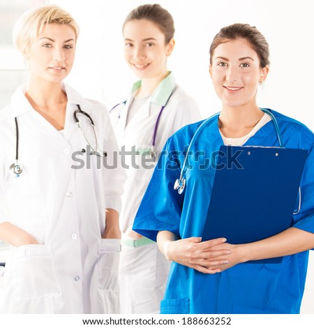 Smiling nurse with two doctors in hospital corridor - stock photo