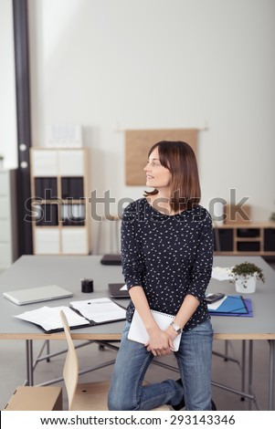 Smiling Office Woman Leaning her Back Against the Table at the Boardroom While Looking Into Distance - stock photo
