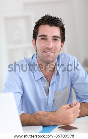 Smiling office worker at work - stock photo
