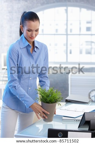 Smiling office worker girl moving plant pot from table.?
