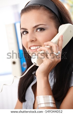 Smiling office worker talking on phone. - stock photo