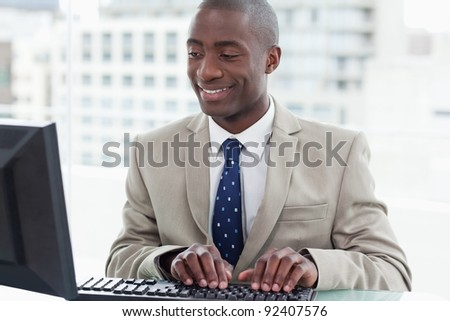Smiling office worker using a computer in his office - stock photo
