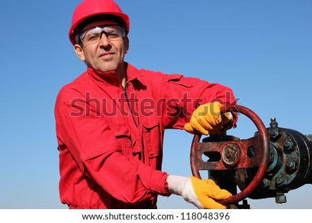Smiling oil worker turning valve on oil rig. Portrait of a worker in action at pump jack oil well. - stock photo