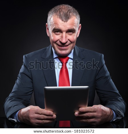 smiling old business man working on his tablet pad computer at his office desk - stock photo