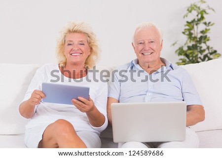 Smiling old couple using a laptop and the tablet on the sofa